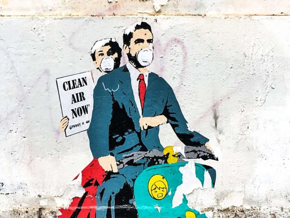 "graffiti of man + woman on moped with sign ""Clean Air Now"""